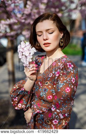 Portrait Of A Cute And Beautiful Woman Girl In A Dress In The Garden In The Middle Of Blooming Sakur