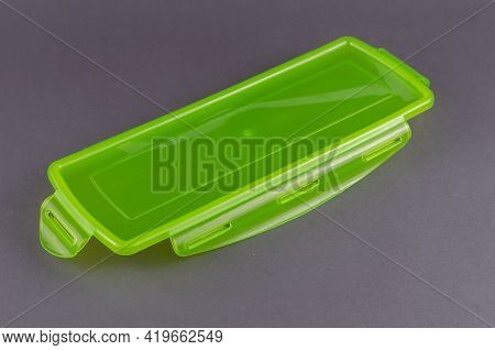 Green Plastic Lid For Food Container. Transparent Rectangular Lid On Gray Background.
