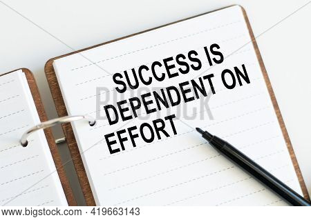 Business Concept. Notebook With Text Success Is Dependent On Effort