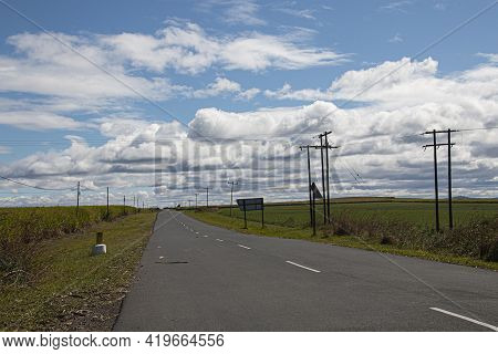 Straight Tarred Road Through Green Sugar Cane Field