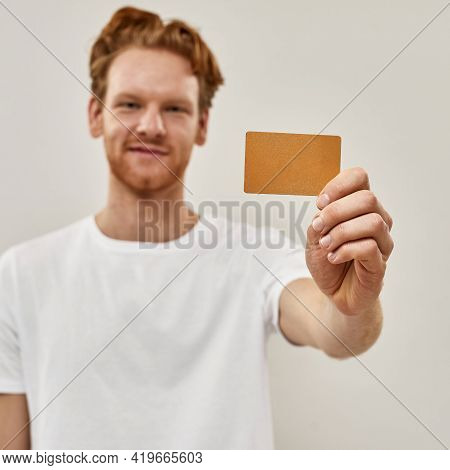Young Redhead Man Holds Credit Card In Front Of Him, Focus Cought On The Credit Card , Man Smiles An