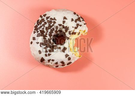 Bitten Tasty Donut On A Pink Background. Top View