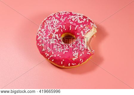 Bitten Tasty Pink Donut On Pink Background. Top View