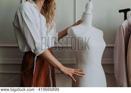 Designer holding a dummy mannequin