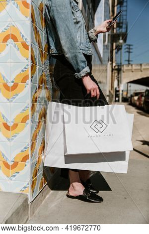 Woman with multiple shopping bags and a smartphone after a shopping spree downtown