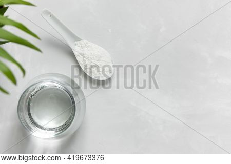 Collagen Powder In A Spoon And A Glass Of Water On A Gray Concrete Background With A Copy Space. Ext
