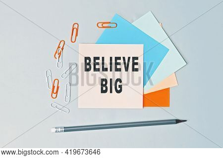 Believe Big - Text On Sticky Note Paper On Gray Background. Closeup Of A Personal Agenda. Top View