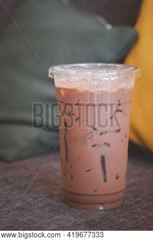 Iced Mocha Coffee In Plastic Glass Place On Gray Burlap Sofa And Pillow.