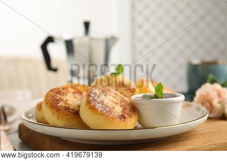 Delicious Cottage Cheese Pancakes With Jam, Mint And Icing Sugar On Wooden Board
