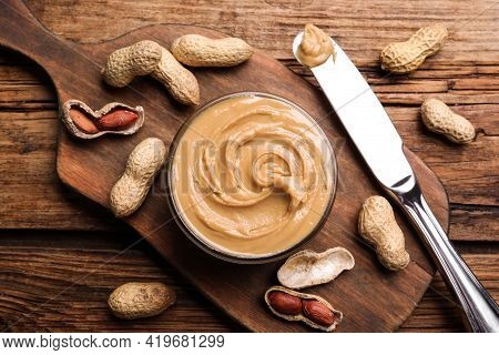 Yummy Peanut Butter In Glass Bowl On Wooden Table, Flat Lay