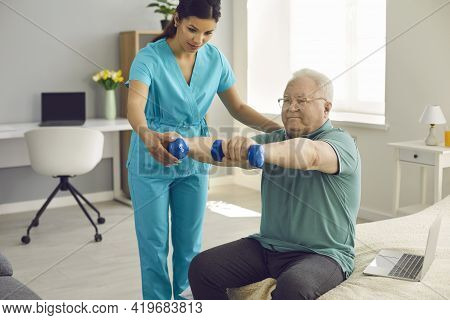 Physiotherapist Or Home Care Nurse Helping Senior Patient Do Rehabilitation Exercise