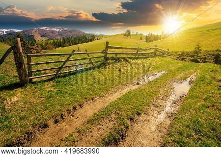 Mountainous Rural Landscape At Sunset In Spring. Path Through Grassy Field. Wooden Fence On Rolling