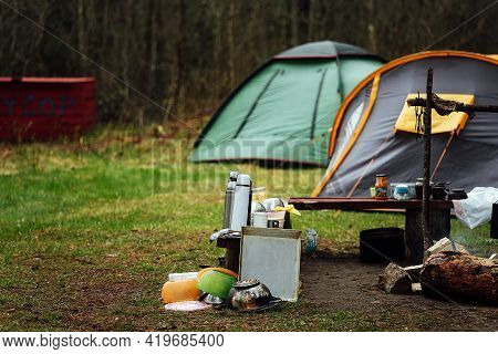 Tourist Tents In The Forest. A Group Of Travelers Set Up Camp In Nature. Vacation In The Country In
