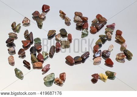 Red And Multicolored Jasper Polished Tumblestones As Nice Natural Background On Mirror