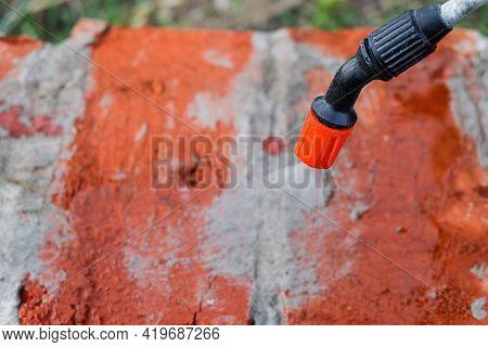 Moisturizing Surface Of Red Ceramic Brick Masonry Using. Spray Gun Under Pressure. Watering Construc