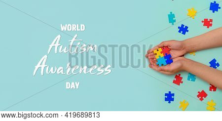 Autistic Pride Day. The Hands Of A Small Child Holding Colorful Puzzles On Blue Background. Heart Of