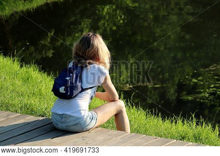 Slim Girl In Short Jeans Shorts With Backpack Sitting On A Beach In A Summer Park. Concept Of Dreami