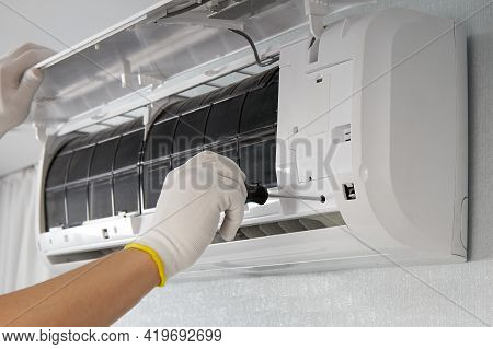 Hands Of A Male Technician Repairing An Indoor Air Conditioner Using A Screwdriver. Maintenance Of A