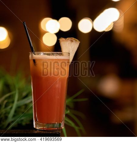 Glass With Orange Cocktail Beverage With Lemon Slice And Straw Against Of Blurred Backlit Background