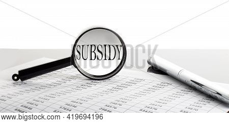 Magnifying Glass With Text Subsidy On Background With Pen