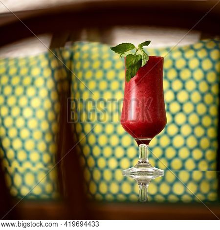 Glass Of Red Berry Drink With Mint. Alcoholic Or Non-alcoholic Cocktail On A Mirror Table Against Of