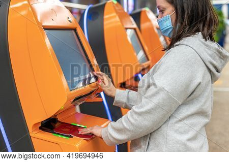 Woman Wearing A Protective Mask Against Coronavirus Travelling By Plane And Doing Self Check In At T