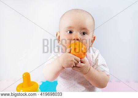 Portrait Of A Newborn Baby Of Caucasian Appearance Sitting On The Floor And Holding A Toy In His Mou