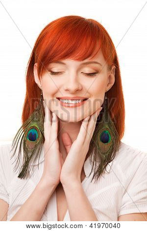 portrait of young beautiful redhead woman with peacock earrings and closed eyes