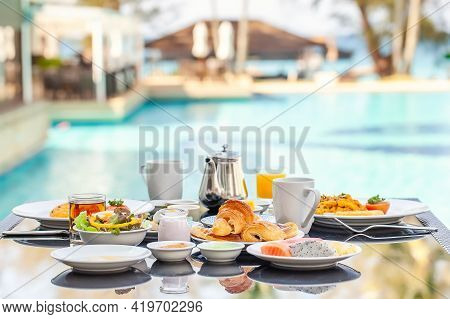 American Breakfast Set On Table Next To Poolside In Resort. English Morning Food Near Swimming Pool