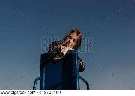Smiling Young Woman In Black Jacket Sitting On Chair In Front Of Blue Sky Enjoying Bright Sunlight.