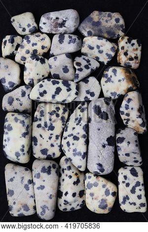 Dalmatian Jasper Heap Jewel Stones Texture On Black Background