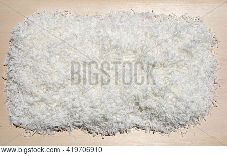 Pile Stack Of Raw Organic Coconut Shavings Sweet Treat Food Background On Wood Cutting Board
