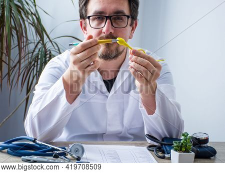 Doctor At Workplace In Office During Appointment Looks Into Camera, Shows Patient Anatomic Model Of