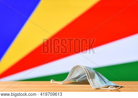 A Medical Mask Lies On The Table Against The Background Of The Flag Of Seychelles. The Concept Of A