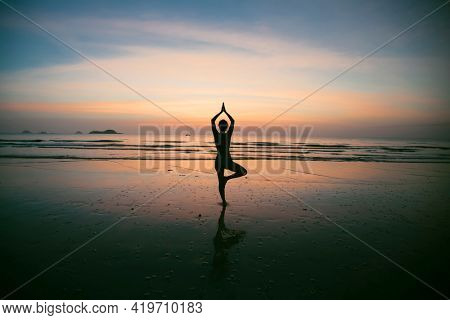 Silhouette of the Yoga woman meditating on the sea beach.
