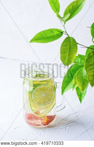 Glass Mug With Handle With Refreshing Detox Lemonade With Sliced Lime, Lemon, Cucumbers And Red Oran