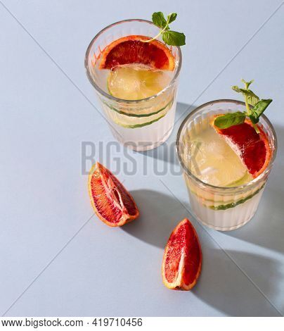 Two Glasses Of Refreshing Summer Lemonade With Ice, Slices Of Lemons And Red Oranges With Sprigs Of