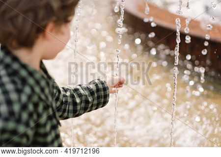 Curly Boy Playing At The Fountain. Boy Plays In The Square Between The Water