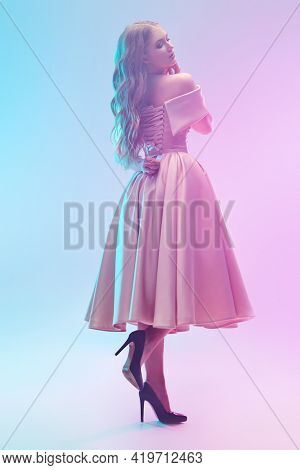 A beautiful girl in an elegant evening dress poses at the studio in gentle pink and blue light. Evening fashion.