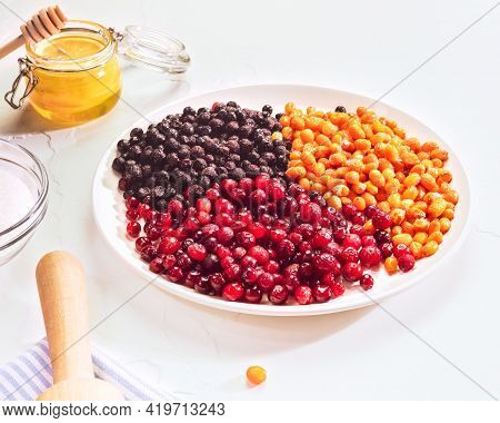 A Horizontal Composition With Frozen Sea Buckthorn, Cranberry And Blueberry Berries On A White Plate