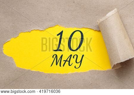 May 10. 10th Day Of The Month, Calendar Date. Hole In Paper With Edges Torn Off. Yellow Background I