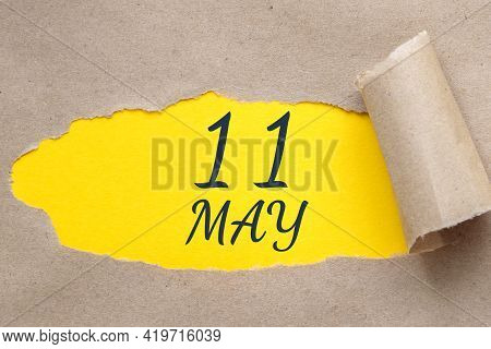 May 11. 11th Day Of The Month, Calendar Date. Hole In Paper With Edges Torn Off. Yellow Background I
