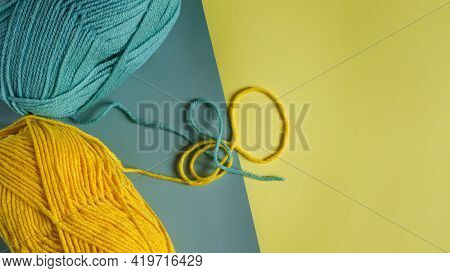 Skeins Of Green And Yellow Yarn On A Two-tone Yellow-green Background Close-up View From Above