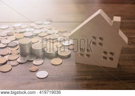 Real Estate And Buy House Concept, Stacked Of Lots Coins On Wood Table With Model House, Saving Mone