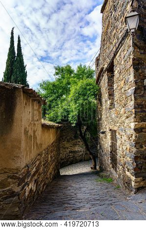 Narrow Alley With Old Stone Houses And Blue Sky With Clouds, Cypress Trees And Stray Cat. Patones De