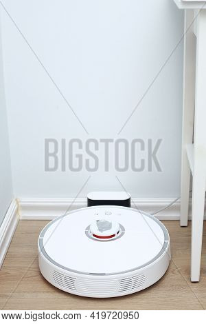 Robotic Vacuum Cleaner On Laminate Wood Floor Charging From Base Station. Smart Cleaning Technology.