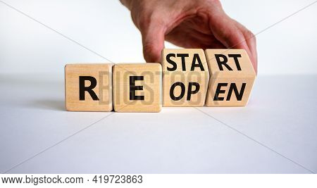 Reopen And Restart Symbol. Businessman Hand Turns Cubes And Changes The Word 'reopen' To 'restart'.