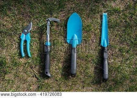 Top View Of A Pruner Rake And A Gardeners Shovel With Blue Handles On The Grass. A Set Of Tools For