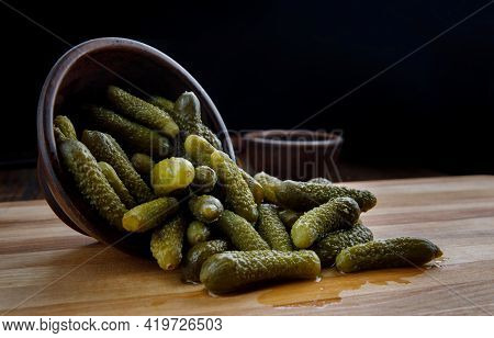 Juicy Crispy Pickled Cucumbers Are Poured From A Clay Cup Onto A Wooden Cutting Board. Salted Cucumb
