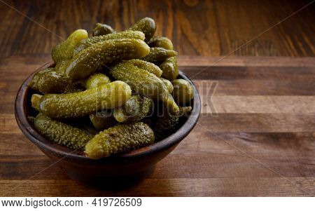 A Cup Of Crispy Pickled Cucumbers Stands On A Wooden Cutting Board. Salted Cucumbers.